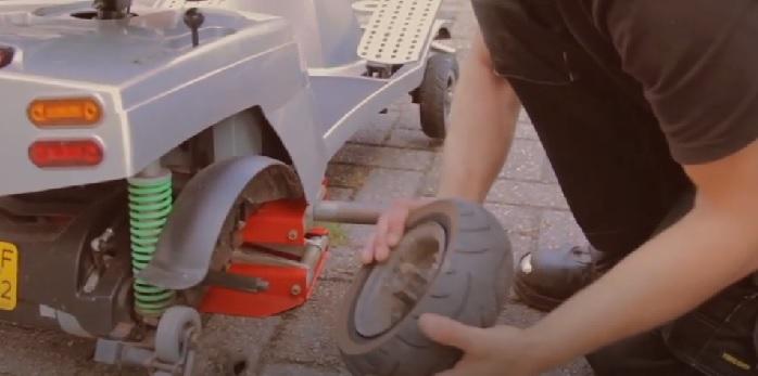 Quingo monteur gaat een lekke band scootmobiel repareren